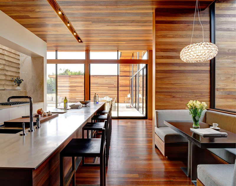 Dining Room Idea - Create A Built-In Dining Nook // This built-in wooden dining nook with gray upholstered cushions, is located just off the kitchen. A pendant light helps to define the dining space, while large windows brighten the shared area. #DiningNook #BuiltInDiningNook #BanquetteSeating #DiningRoom