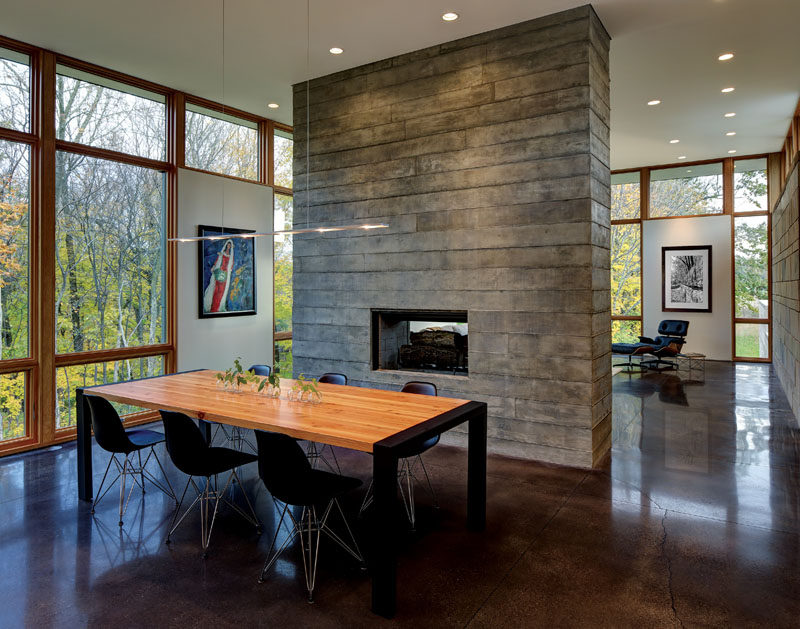 Fireplace Design Idea - 6 Different Materials To Use For A Fireplace Surround // This concrete fireplace surround also doubles as a room divider in this home.