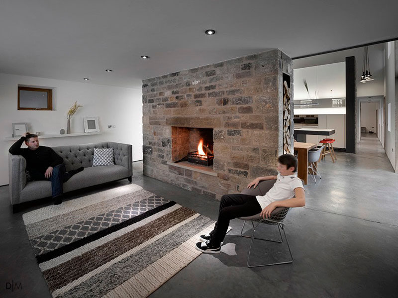 Fireplace Design Idea - 6 Different Materials To Use For A Fireplace Surround // An original stone fireplace surround has been kept in this renovated barn that's now a home. #FireplaceSurround #FireplaceIdeas #StoneFireplaceSurround