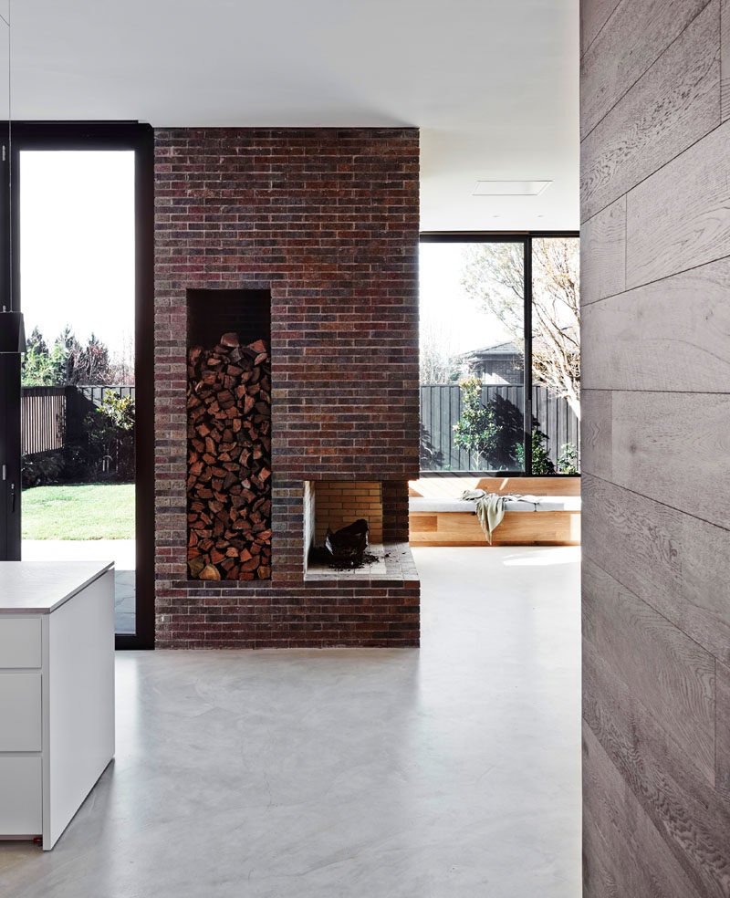 Fireplace Design Idea - 6 Different Materials To Use For A Fireplace Surround // Deep red bricks have been used to create the fireplace surround that incorporates wood storage. #FireplaceSurround #FireplaceIdeas #BrickFireplaceSurround