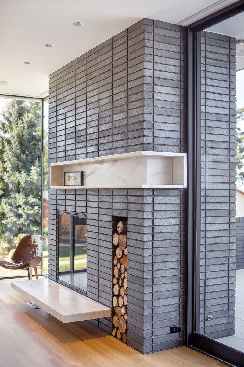 Fireplace Design Idea - 6 Different Materials To Use For A Fireplace Surround // This light grey brick fireplace surround that a built-in shelf and firewood storage. #FireplaceSurround #FireplaceIdeas #BrickFireplaceSurround