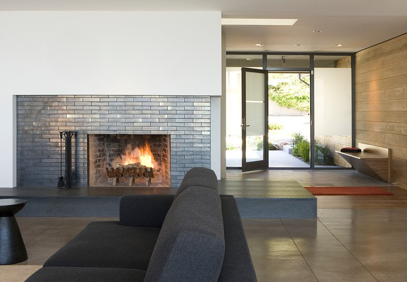 Fireplace Design Idea - 6 Different Materials To Use For A Fireplace Surround // Glazed brick-shaped tiles have been used as a fireplace surround this home.