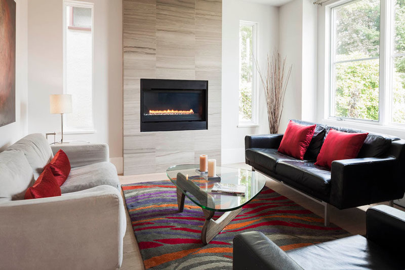 Fireplace Design Idea - 6 Different Materials To Use For A Fireplace Surround // Large light-colored tiles have been used as a fireplace surround this home. #FireplaceSurround #FireplaceIdeas #TileFireplaceSurround