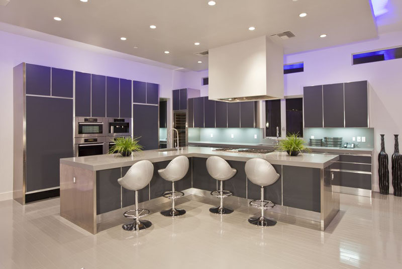 12 Examples Of Sophisticated Gray Kitchen Cabinets // Futuristic chairs and lighting as well as the dark gray cabinetry make this kitchen feel super modern.