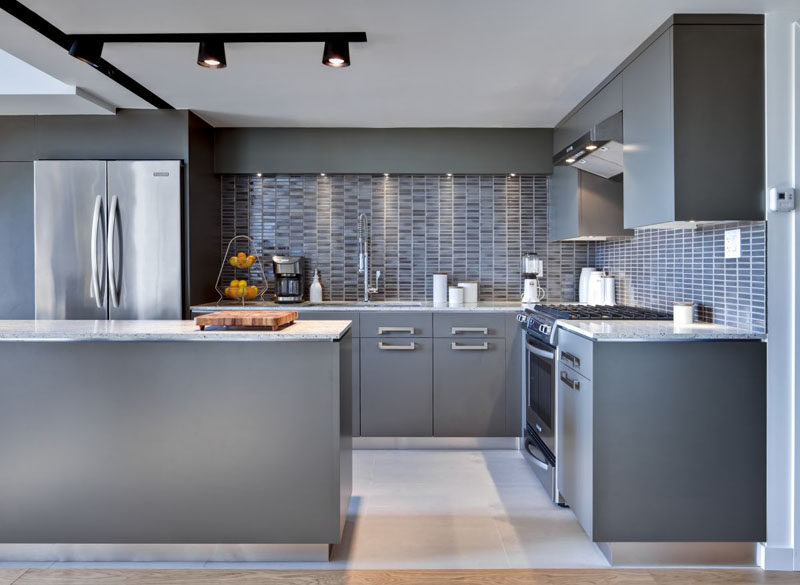 12 Examples Of Sophisticated Gray Kitchen Cabinets // The way the lights are positioned in this kitchen creates shadows on parts of the cabinets but not on others, making the cabinets look like they've been painted different shades of grey.