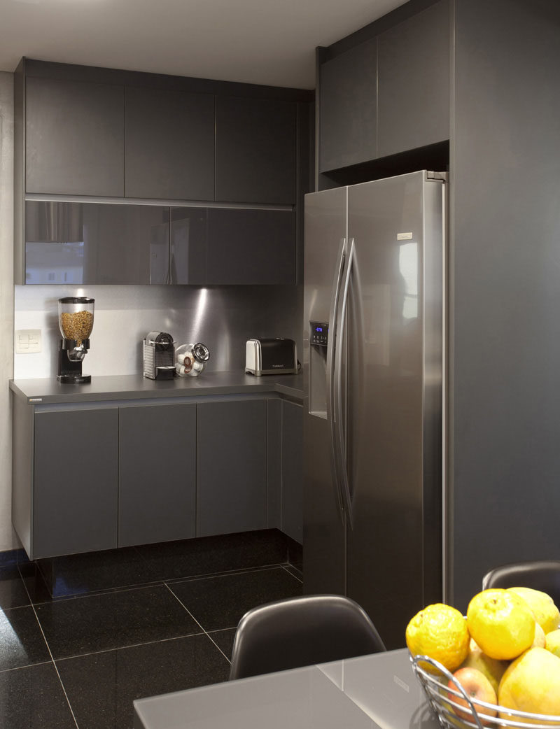 12 Examples Of Sophisticated Gray Kitchen Cabinets // Gray cabinets in both matte and glossy finishes add dimension and sophistication to this modern kitchen.