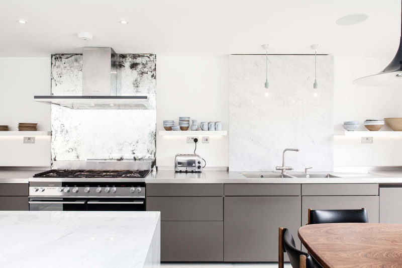 12 Examples Of Sophisticated Gray Kitchen Cabinets // The gray cabinets along the bottom half of the kitchen make it feel modern and new, while the vintage mirror behind the stove makes the space feel personalized and lived in.