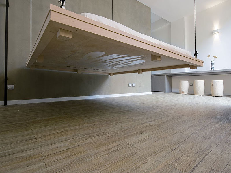 In this small apartment, the bed can be hoisted up to the ceiling to make way for a living area.