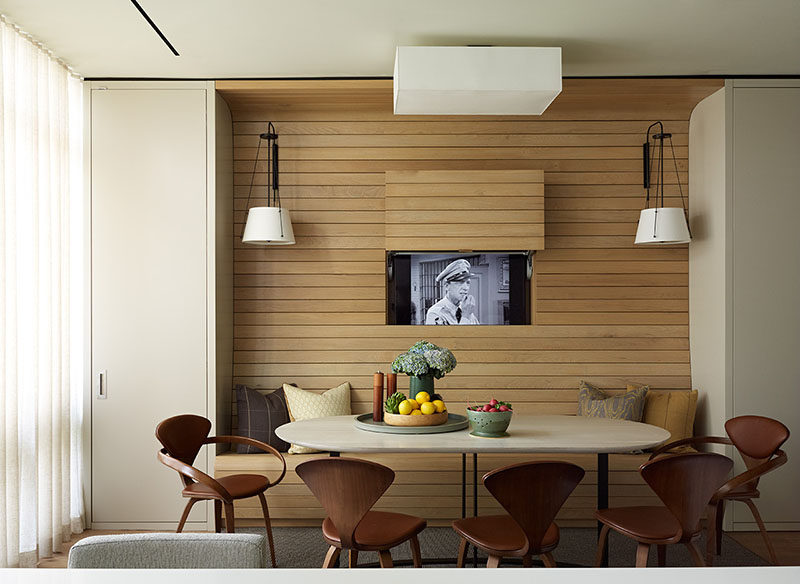 In this apartment, the television was placed behind a panel within the walnut wall, allowing it to be visible for when you want to watch tv, but at the same time, can be completely hidden away without the use of a bulky cabinet.