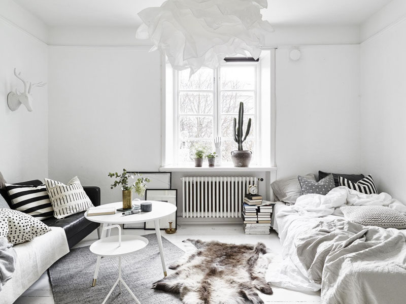 Apartment Decor Idea - Decorate With Textiles // Billowy blankets, piles of pillows, and layered rugs give this tiny apartment texture, depth, and warmth even though the colors are super neutral.