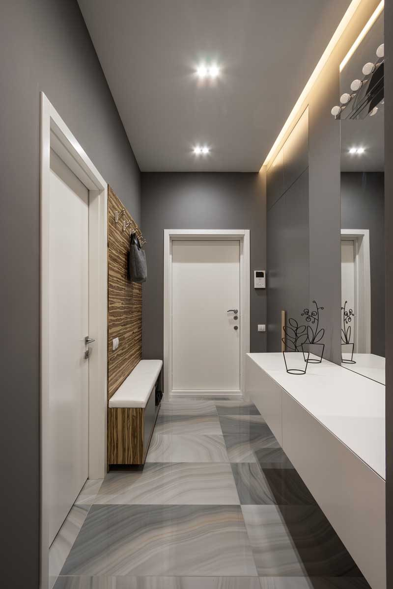 This grey entryway in this apartment has a slim built-in bench and wooden panel with hangers on one side, and on the opposite wall hangs a floating cabinet.