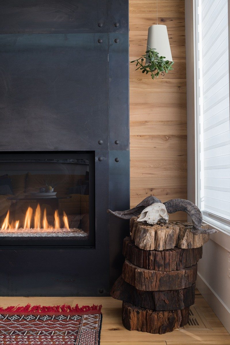 A black fireplace surround has been paired with a wood wall and wood floor in this home.