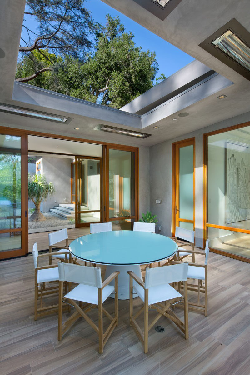 This home has a partially covered outdoor dining area with round dining table.