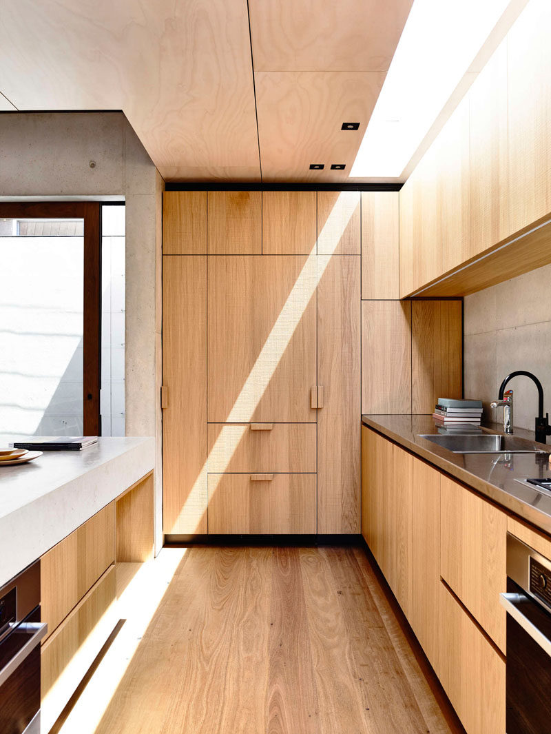 Kitchen Design Idea - 10 Inspirational Examples Of Kitchens With Integrated Fridges // Wooden cabinetry in this kitchen hides the the fridge and makes this kitchen feel more cohesive and unified.