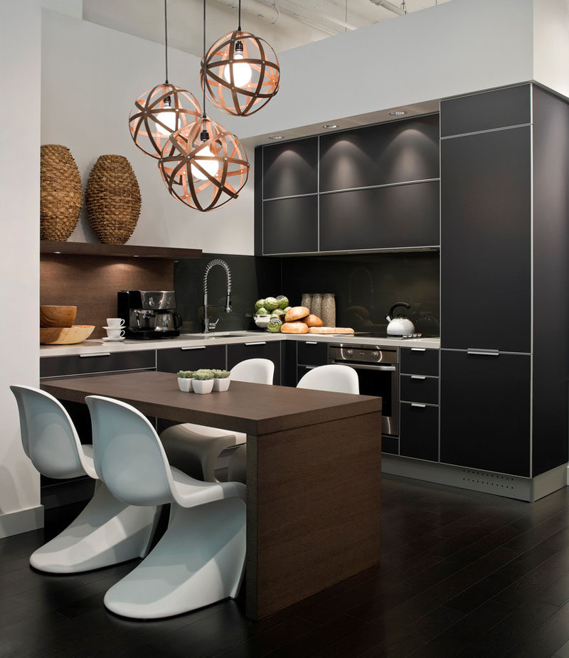 Kitchen Design Idea - 10 Inspirational Examples Of Kitchens With Integrated Fridges // The black cabinetry in this kitchen also covers the fridge and creates a sleek, modern looking kitchen.