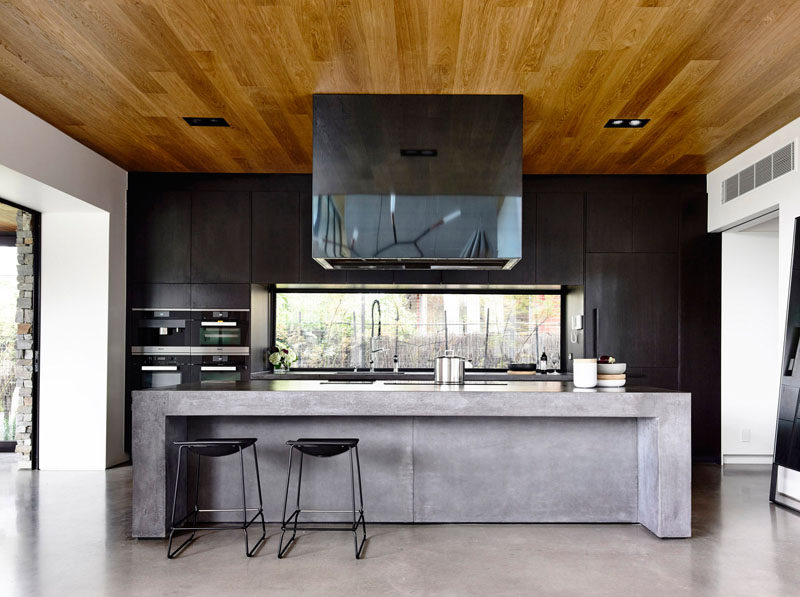 Kitchen Design Idea - 10 Inspirational Examples Of Kitchens With Integrated Fridges // Black cabinets do an excellent job of concealing this fridge by blending the lines and making the whole back wall of the kitchen appear seamless.