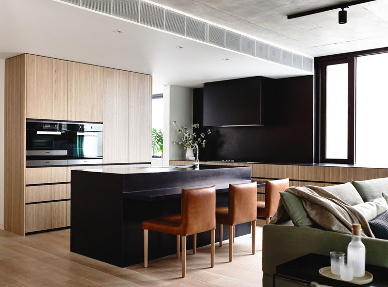 Kitchen Design Idea - 10 Inspirational Examples Of Kitchens With Integrated Fridges // The absence of a stand alone fridge makes this kitchen feel bigger and brighter, and lets the contrast between the black and the wood really stand out.
