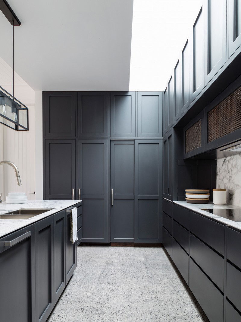 Kitchen Design Idea - 10 Inspirational Examples Of Kitchens With Integrated Fridges // A fridge is hidden behind these dark panels of this cabinetry of this kitchen.