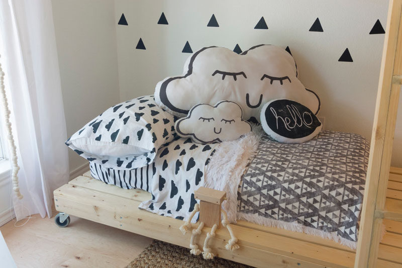 This gender neutral kids room features bright white walls, simple modern decor and custom made wooden beds. The bottom bed even has wheels on it so that it can be moved around when needed.