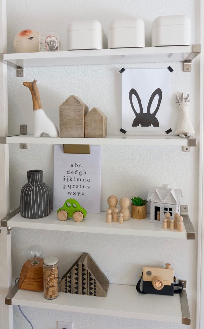 Personal mementos and minimalist toys on the shelves of this kids room add a sense of fun and whimsy to the room.