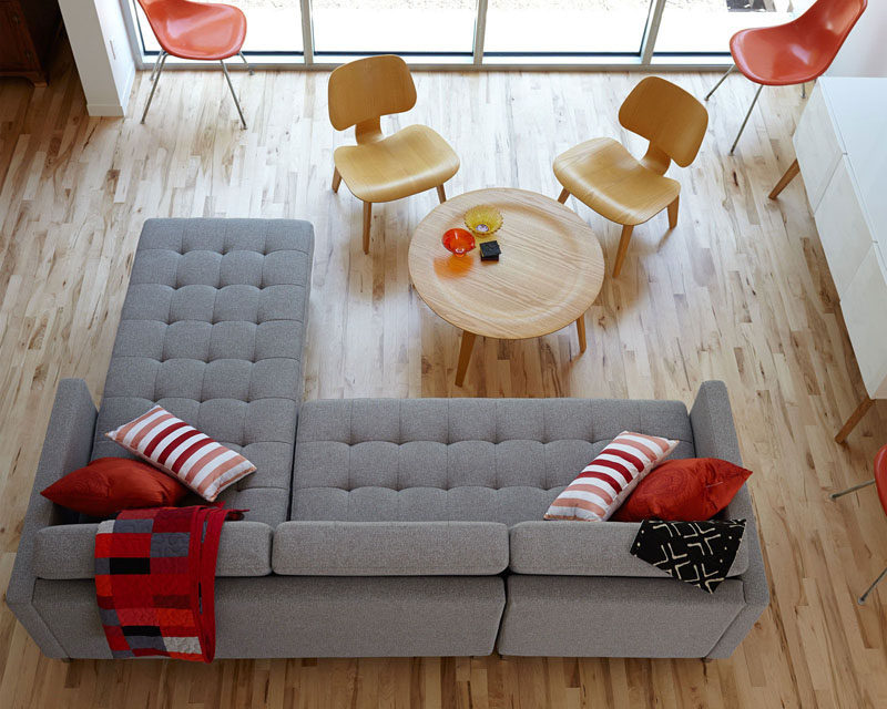 15 Living Room Layouts From Above // The use of light wood and grey help the red accents, like the chairs, pillows, and blanket really pop.