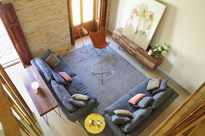 15 Living Room Layouts From Above // The wood paneled windows and the vintage side table, modern furniture, like the grey couches, hairpin table, and glass coffee table, this living room comes off modern and contemporary.