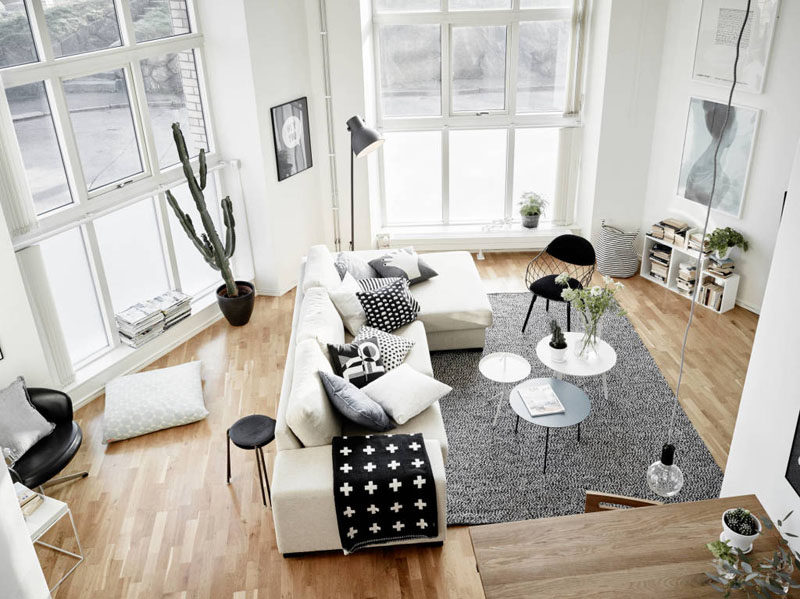 15 Living Room Layouts From Above // Big windows, simple furniture, and lots of pillows make this living room a bright space perfect for getting cozy in. A gray rug helps to anchor the sofa in the oddly shaped room.