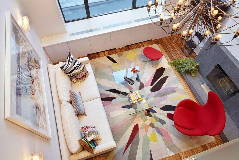 15 Living Room Layouts From Above // The bright rug, chair, and pillows are offset by the white walls and white couch, keeping the room fun rather than overwhelming.