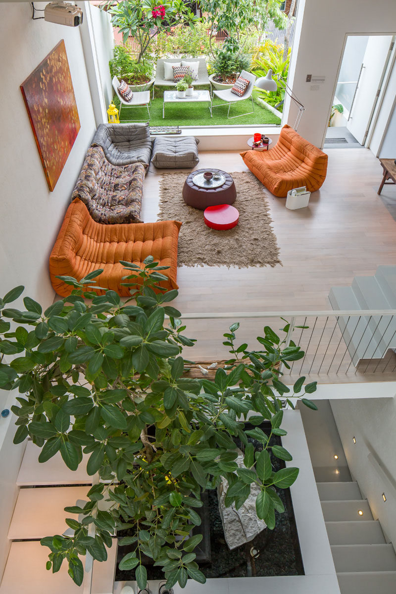 15 Living Room Layouts From Above // The painting on the wall ties all the colors in the living room together and makes the orange couches really blend in with the rest of the decor.