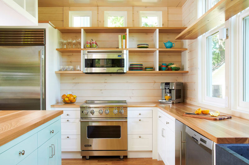 Kitchen Design Idea - Open Shelving (19 Photos) // These wooden shelves are deep and divided, but lack cupboard doors which makes the fun colored plates and mugs act as kitchen decor.