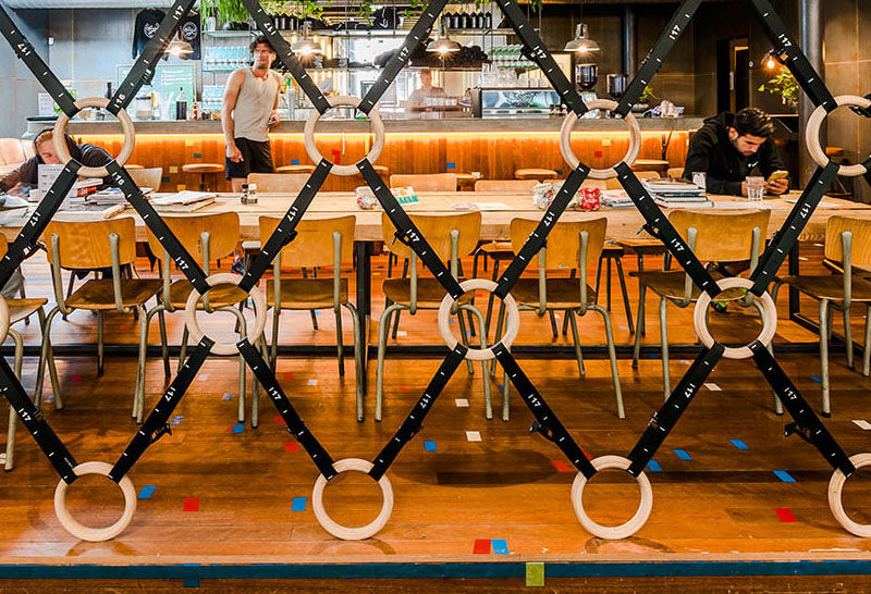 Room Divider Idea - The designers of this gym in Amsterdam made a room divider out of wooden gymnastic rings and straps, to separate the gym area from the bar/food area.