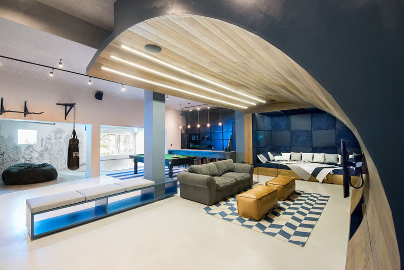 This basement designed for a teenager features a wooden wave, a bar/snack area, a skate bowl, arcade games and a workout area.