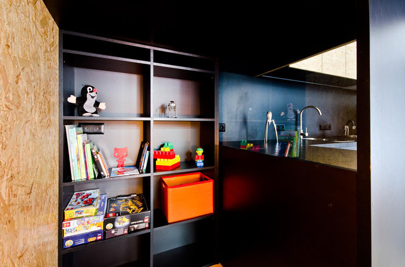 A small hiding room for a child has been tucked into a space behind a desk and a kitchen.