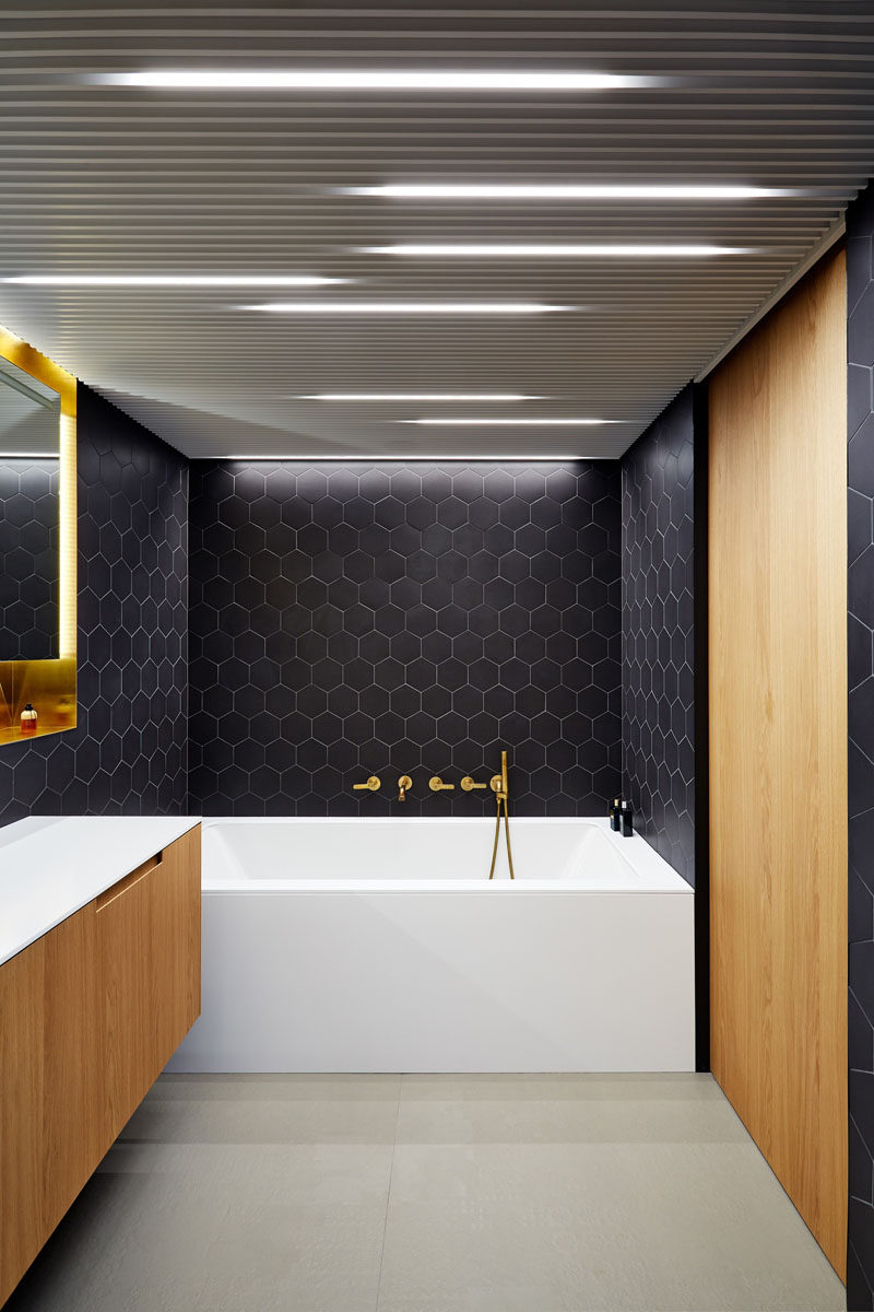 Bathroom Design Idea - Often black in bathrooms can make them feel dark and closed in, but in this Prague apartment architect Lenka Míková, combined black with brass, white and wood to give it a contemporary, luxurious feeling, perfect for a bathroom.