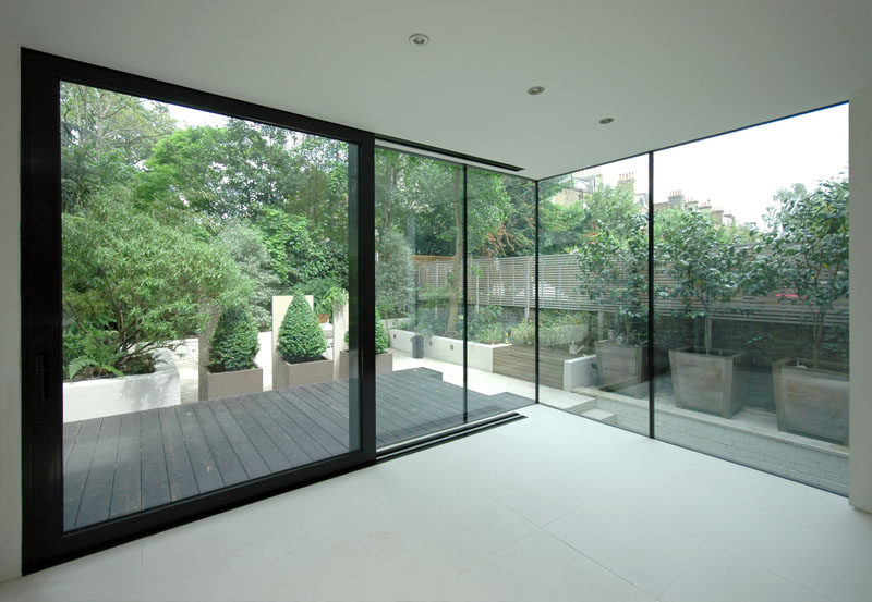 This house extension features corner-to-corner windows and a large sliding door to the patio. Black window and door frames have been used to match to the black wood exterior.