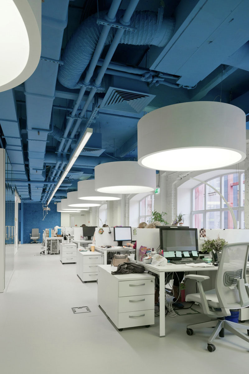 The saturated blue ceiling and wall surrounds bright whites in this media agency's office.