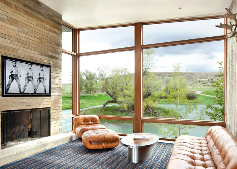 This sitting area with a fireplace has view is of the surrounding hills and river outside.