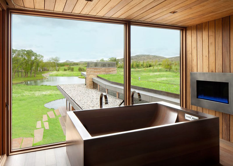 In this bathroom, the wooden bathtub and fireplace make it an idea place to relax and take in the view.