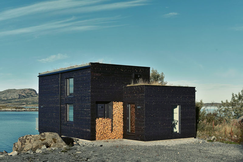 Charred wood siding and a green roof cover this small home on the coastline of Norway.