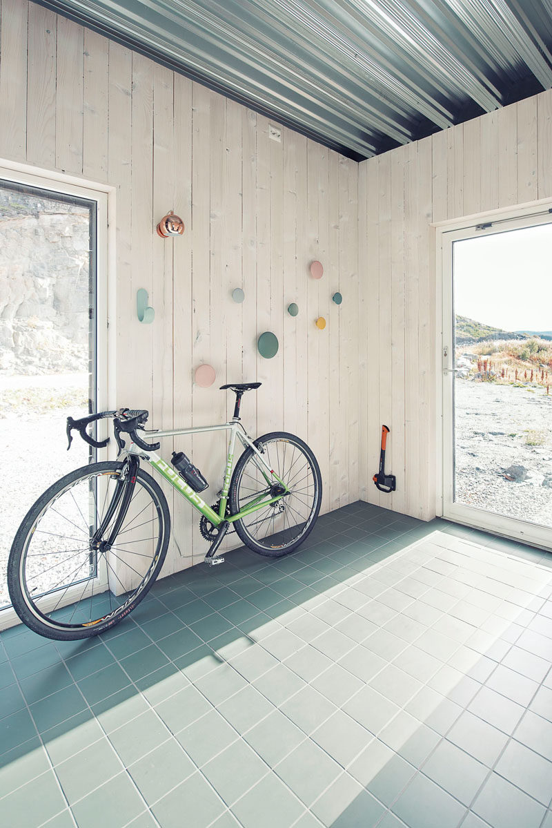As you enter this small house, there's a tile entryway with walls lined with wood, that provides a space for storing a bike, coats and shoes.