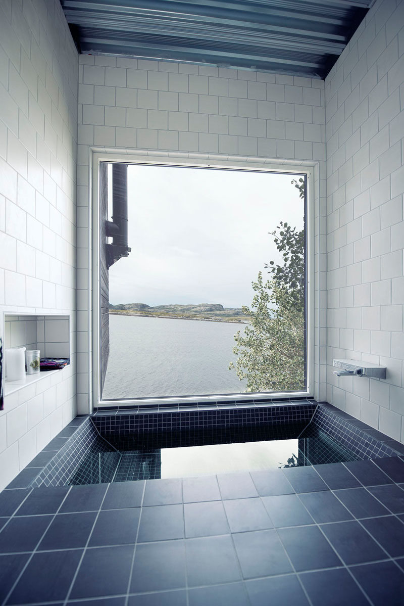 This bathroom in a small home in Norway has a built-in bathtub surrounded by gray and white tiles, and is perfectly positioned for water views.