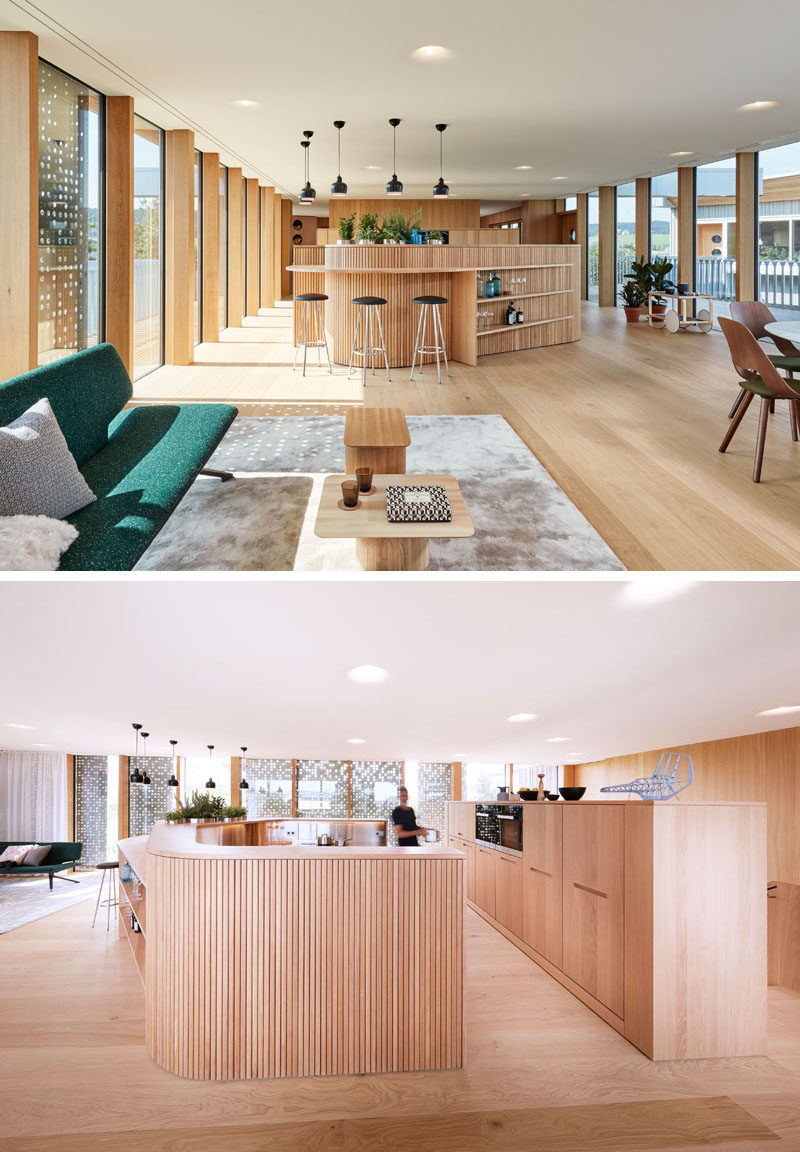 The upper floor of this home is flooded with light from the floor-to-ceiling windows surrounding the living area, and the wood covered curved kitchen has bar seating that transforms into shelving.