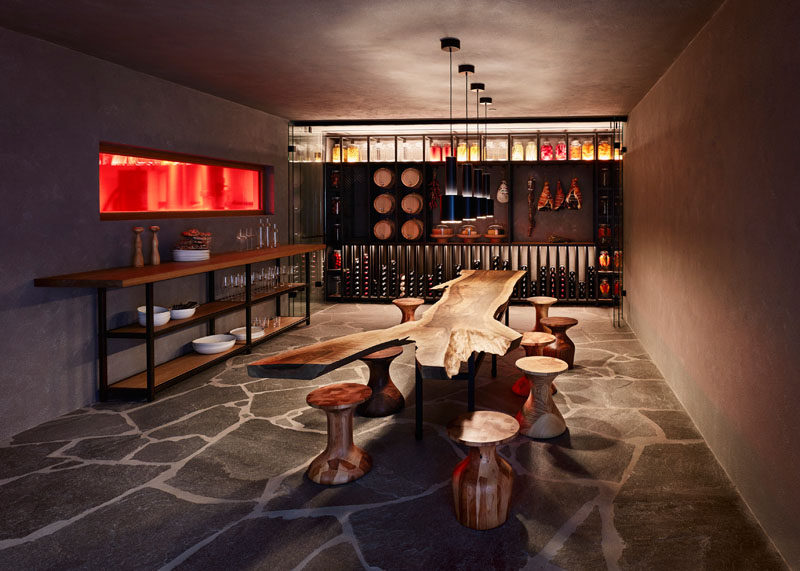 This small cellar has a wall for wine storage, as well as a large live edge wooden table surrounded by wooden stools, ideal for entertaining.