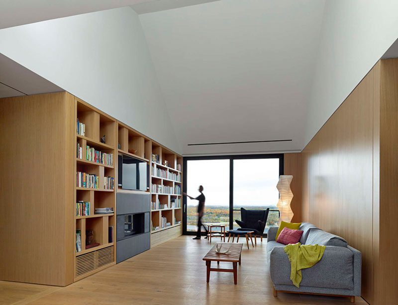 This living area has a wall of shelves filled with books that surround a television and another fireplace.