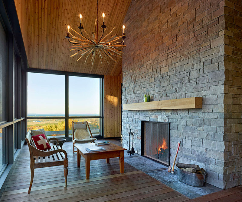 This casual sitting room focused on the fireplace is surrounded by windows and a wood floor and ceiling.