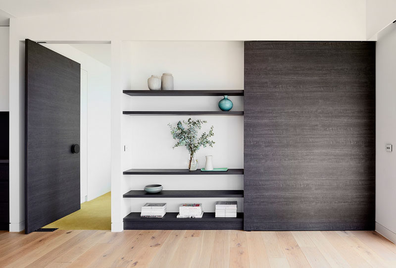 In this house, a custom wooden wall unit displays personal items, and matches the large wooden pivoting door that leads to the bedroom.