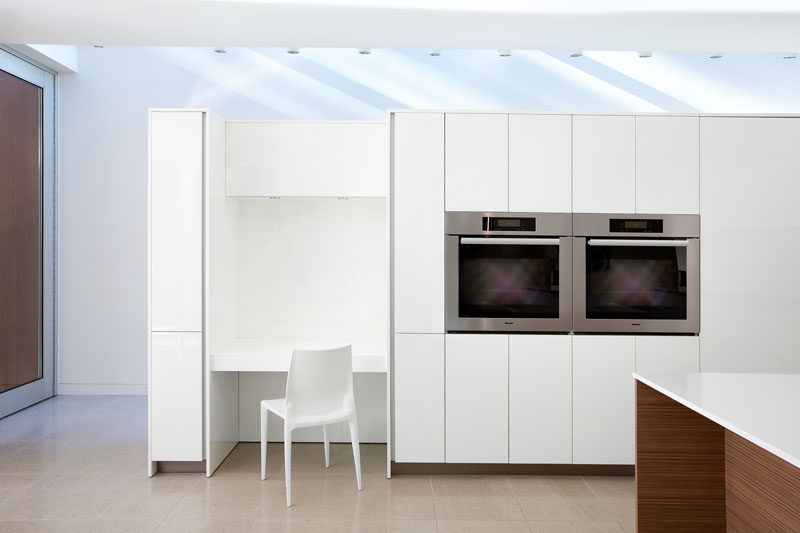 In this mostly white kitchen, a built-in desk has been included in the design that matches the kitchen cabinetry.