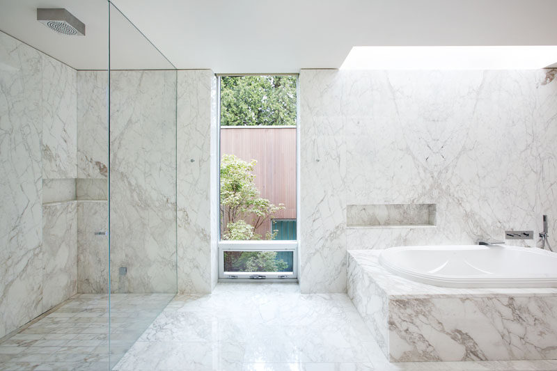In this bathroom, light colored stone has been used for the walls, flooring and bath/shower surrounds.