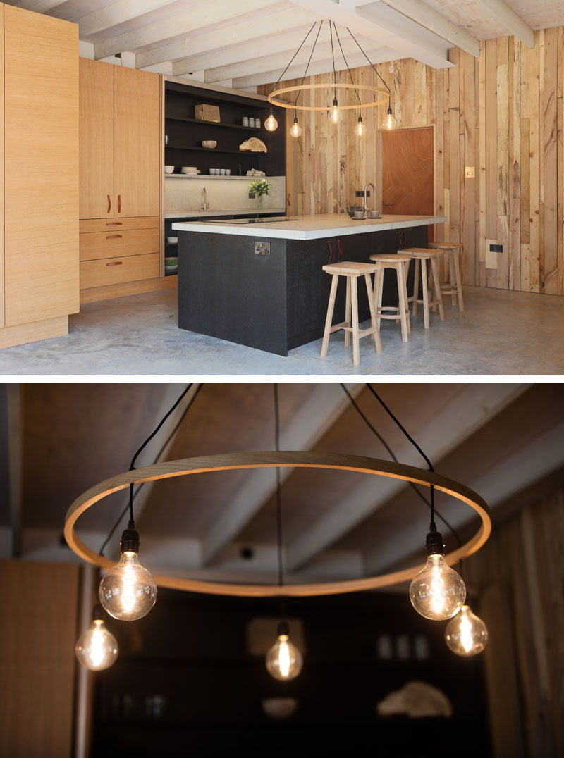 In this kitchen, the island is highlighted by a large hanging light, and the black in the island and cabinetry creates a dramatic contrast against the surrounding wood.