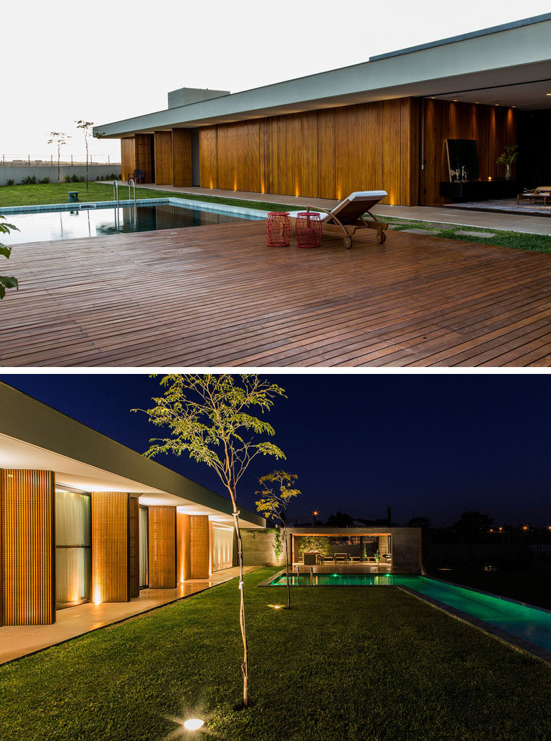 At night, the trees, swimming pool and exterior of this home are all lit up.